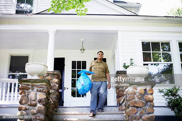 Mature man on porch, carrying plastic bag