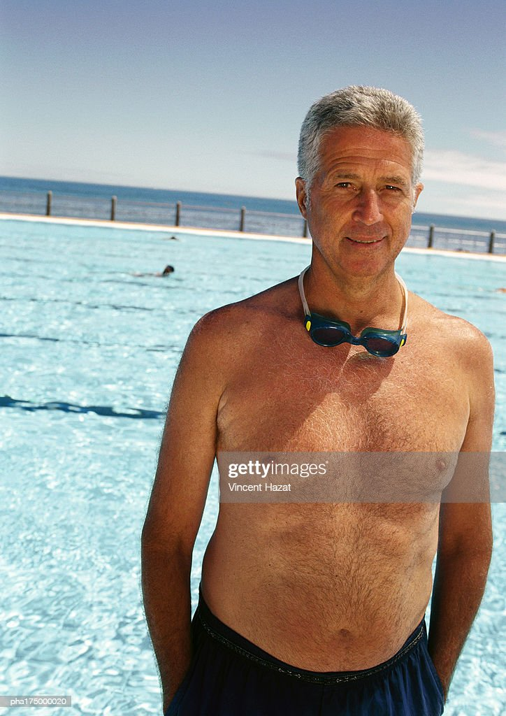 Mature man on side of swimming pool, portrait : Stock Photo