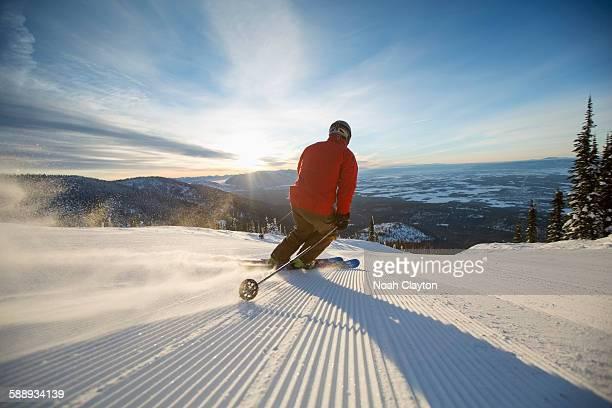 Mature man on ski slope at sunset