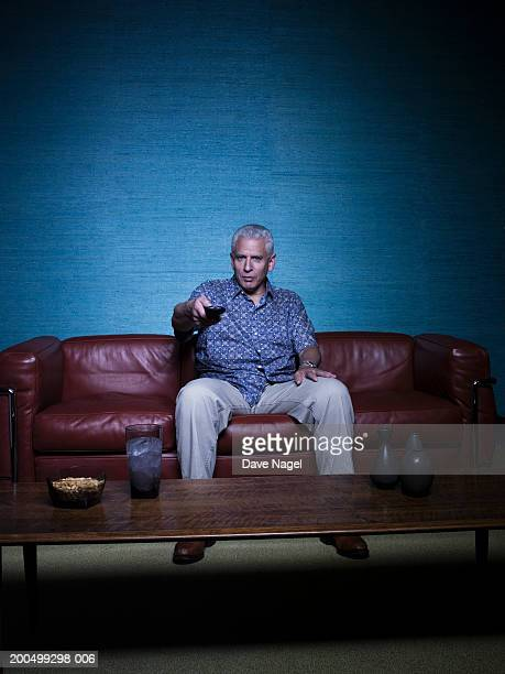 Mature man on sofa, holding remote control, portrait