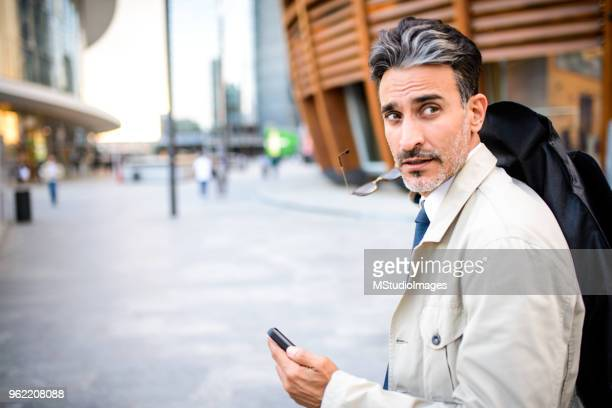 Mature man on the move using mobile phone