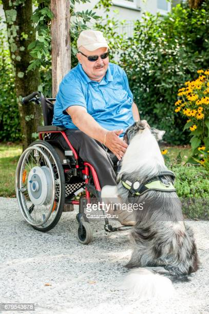 Homme d'âge mûr sur fauteuil roulant ayant des animaux domestiques thérapie à la communauté de retraite