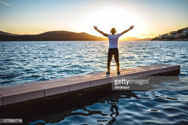 rijpe mens open wapens aan zonsondergang bij kust - gelovige stockfoto's en -beelden