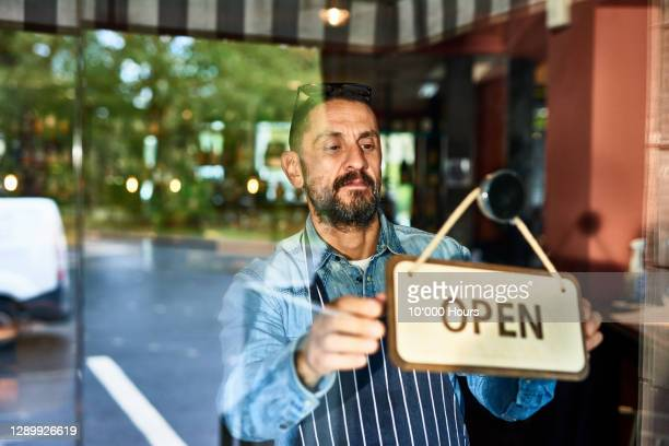 mature man opening restaurant - one mature man only stock pictures, royalty-free photos & images