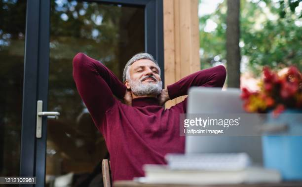 a mature man outdoors by a tree house, meditating. - serene people stock pictures, royalty-free photos & images