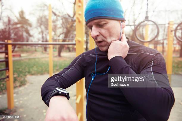 Mature man, outdoors, checking pulse rate, looking at watch