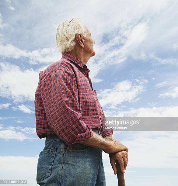 Mature man outdoors, hands resting on wooden stick, low angle view