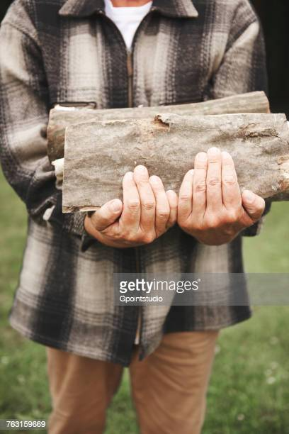 Mature man outdoors, holding firewood, mid section