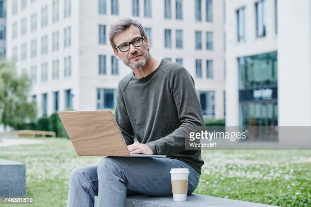 Mature man outdoors with laptop and takeaway coffee