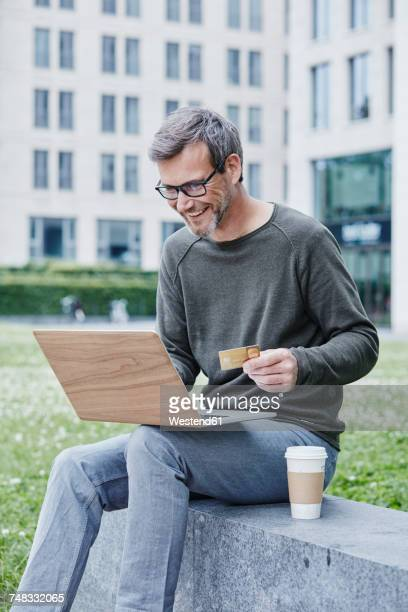 Mature man outdoors with laptop, credit card and takeaway coffee