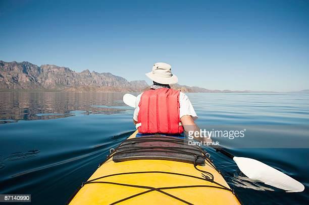 mature man paddling sea kayak