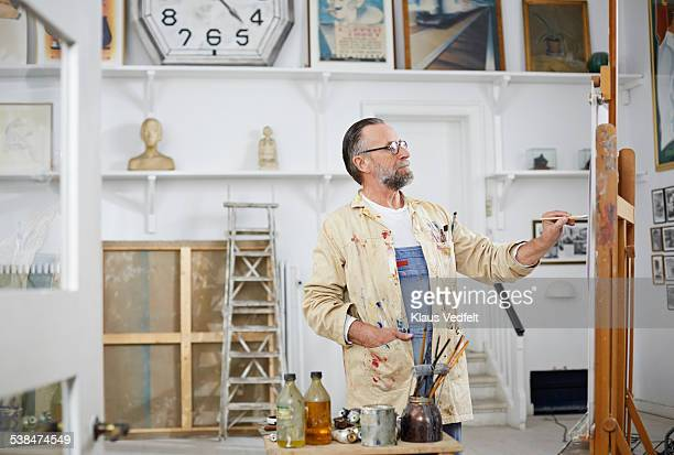 Mature man painting art in his studio