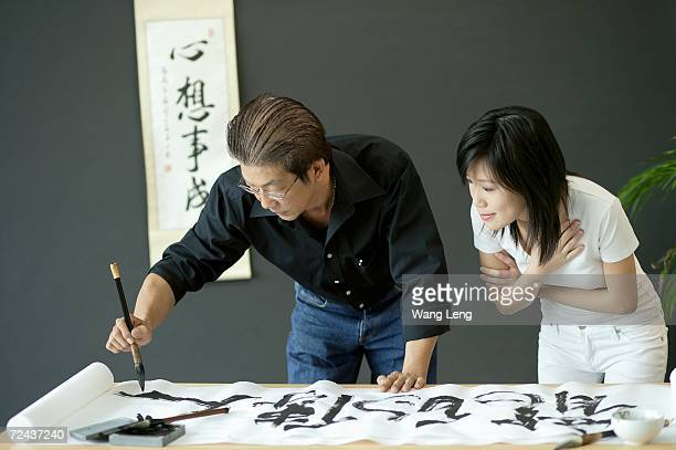 Mature man painting Chinese calligraphy, woman next to him watching