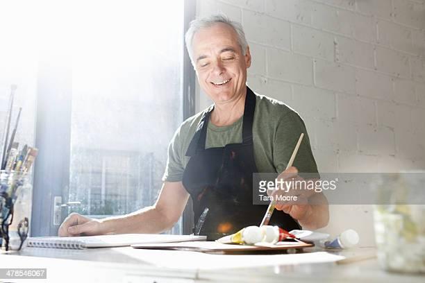 mature man painting in studio - linkshandig stockfoto's en -beelden