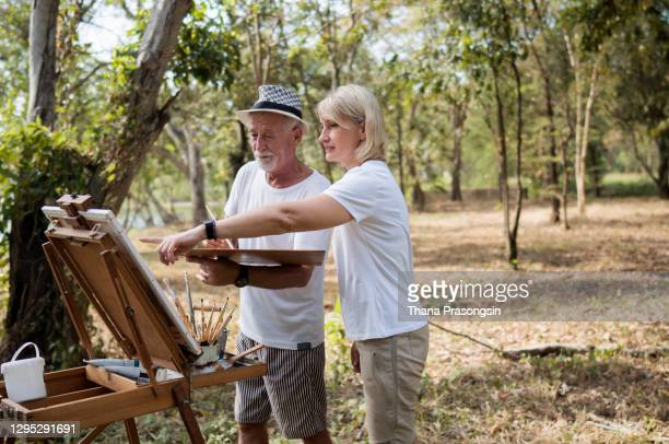 mature man painting on canvas with his wife - painted image stock pictures, royalty-free photos & images