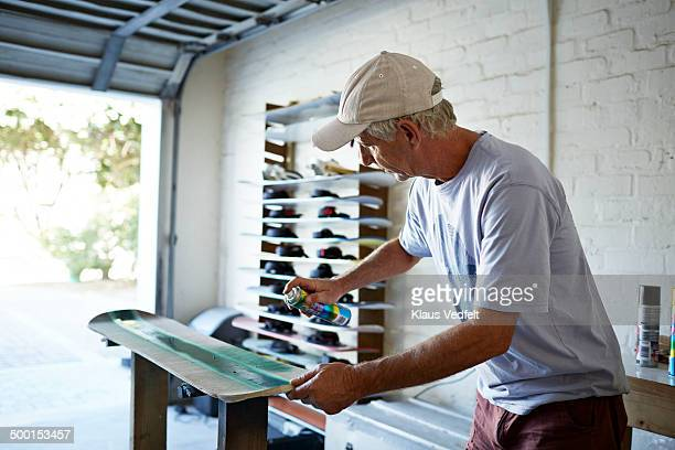 Mature man painting sandboard