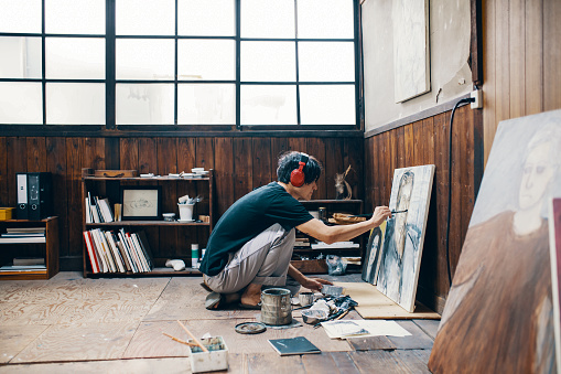 Mature man painting with oil paint in his studio while wearing headphones 1061468532