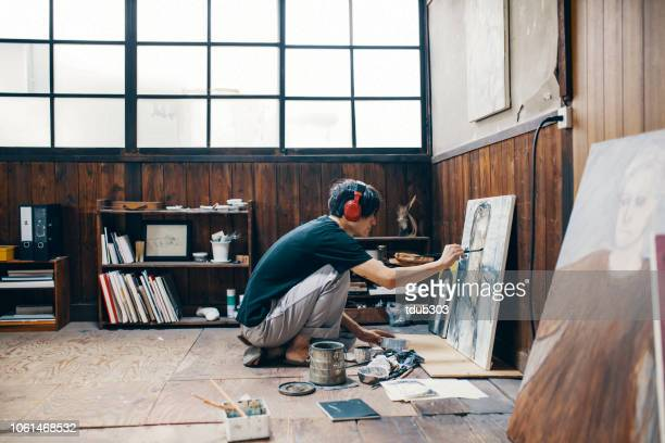 mature man painting with oil paint in his studio while wearing headphones - artist stock pictures, royalty-free photos & images