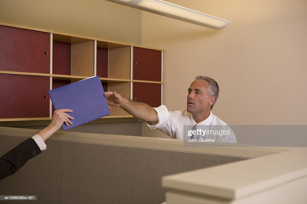 Mature man passing file to woman : Foto stock