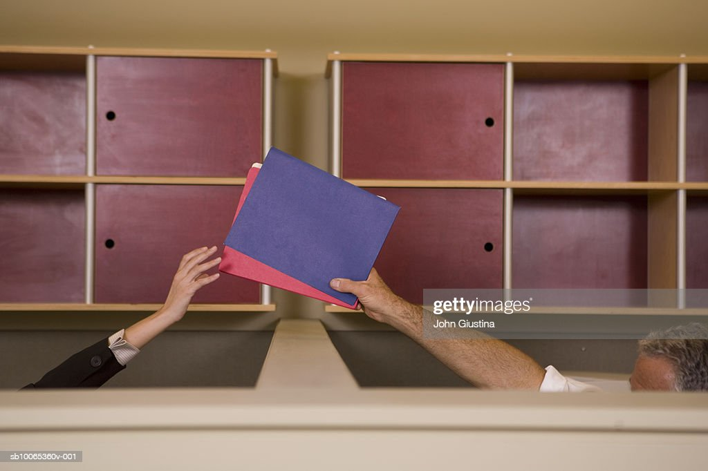 Mature man passing file to woman through office partition : Foto stock