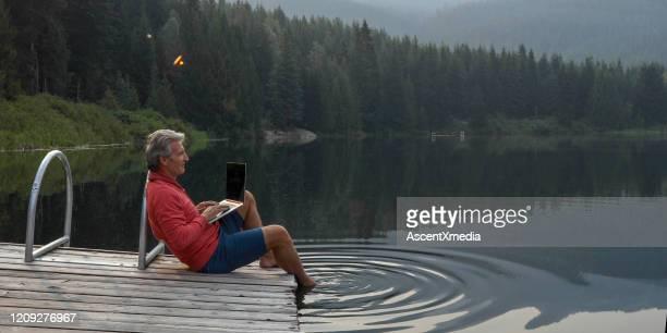 de rijpe mens pauzeert op houten pijler, kijkt uit over meer - gemak stockfoto's en -beelden