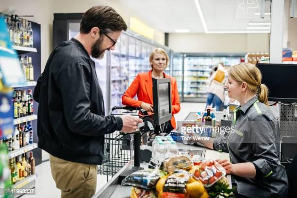 mature man paying for groceries at checkout - partie du corps humain photos et images de collection