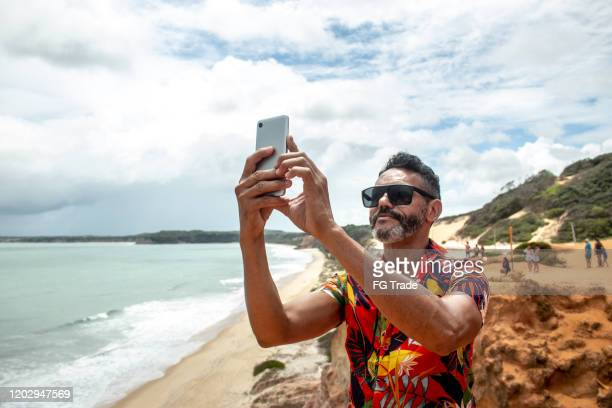 mature man photographing the praia do pipa with mobile phone - natal brazil stock pictures, royalty-free photos & images