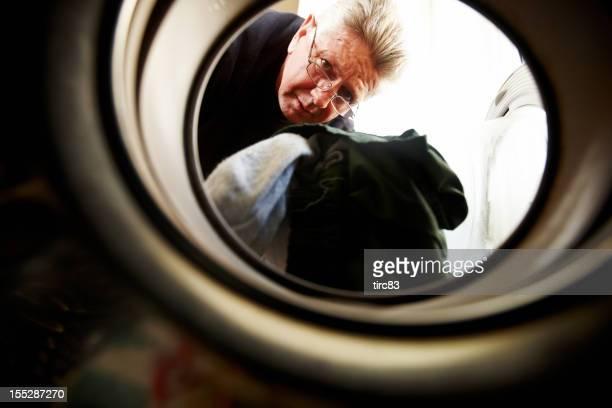 Hombre maduro colocar sucio en la máquina de lavado