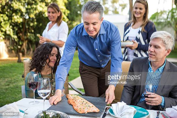 mature man placing fish cuisine on garden party table - putting stock pictures, royalty-free photos & images
