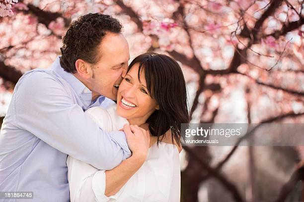 mature man playfully biting his wife's earlobe - earlobe stock photos and pictures