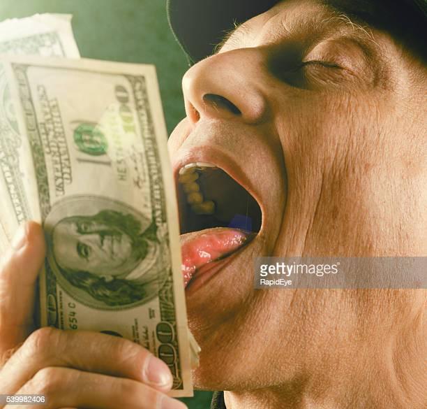 Mature man playfully licking bundle of $100 banknotes