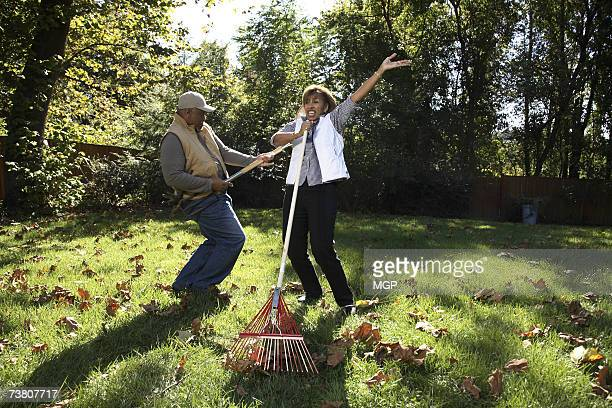 mature man playing air guitar with garden fork, woman singing with rake - young at heart stock pictures, royalty-free photos & images