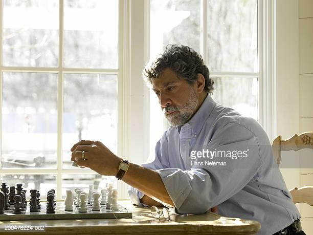 mature man playing chess - hans neleman ストックフォトと画像