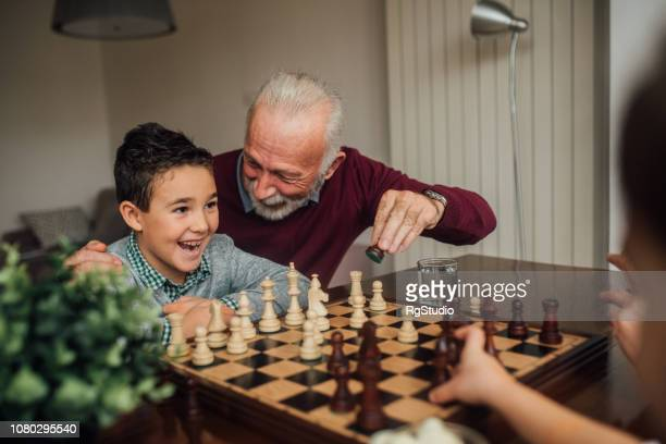 mature man playing chess with grandchild - playing chess stock pictures, royalty-free photos & images