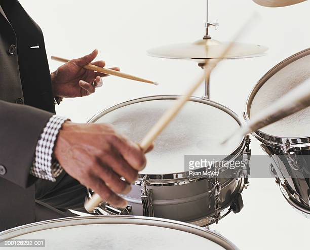 Mature man playing drums, close-up of hands