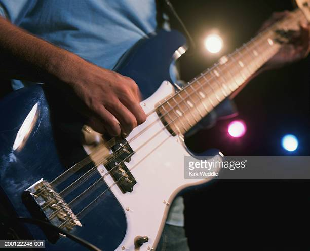 mature man playing electric guitar, mid section - middle bass club stock photos and pictures