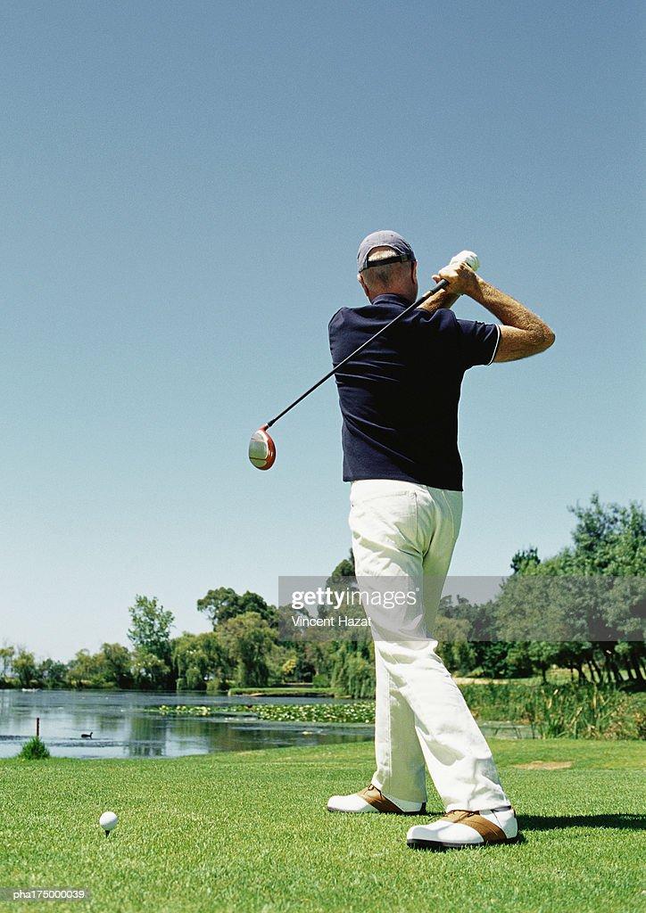 Mature man playing golf, rear view : Stockfoto
