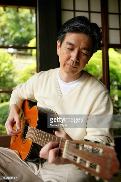 Mature man playing guitar, close-up