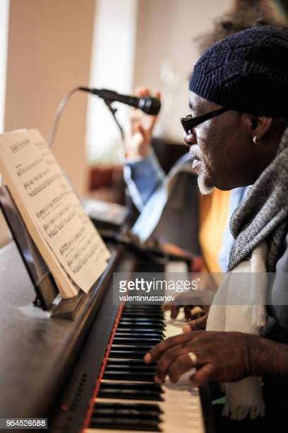 mature man playing piano with young woman - keyboard instrument stock photos and pictures
