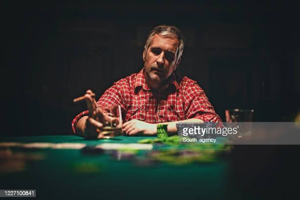 mature man playing poker late by night - gambling table stock pictures, royalty-free photos & images