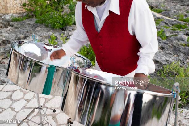 mature man playing steel drums, mid section - steel drum stock photos and pictures