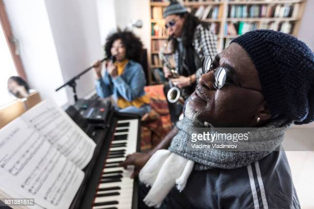 mature man playing the piano with friends - keyboard player stock photos and pictures