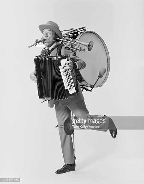 Mature man playing variety of musical instruments on white background