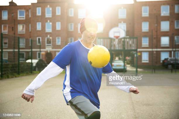 mature man playing with football on football ground in the city - football stock pictures, royalty-free photos & images