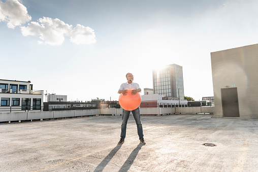 Mature man playing with orange fitness ball on rooftop of a high-rise building - gettyimageskorea