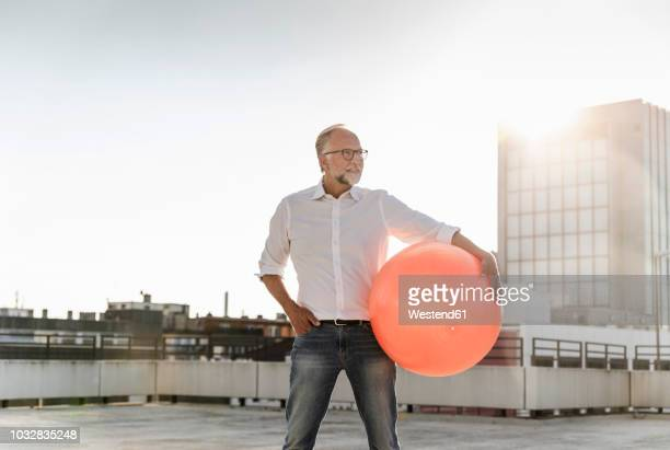 mature man playing with orange fitness ball on rooftop of a high-rise building - spielball stock-fotos und bilder