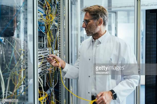 mature man plugging transceiver on fiber optic cable into rack - fibre optique photos et images de collection