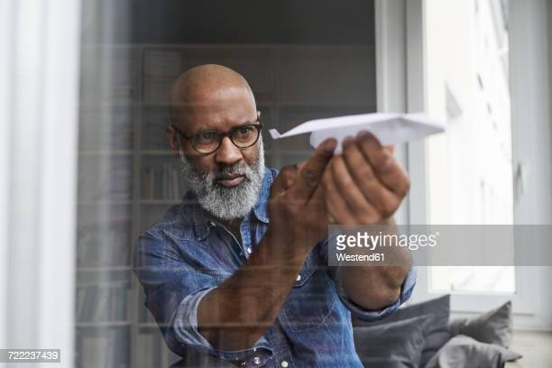 mature man plying with paper plane - young at heart stock pictures, royalty-free photos & images