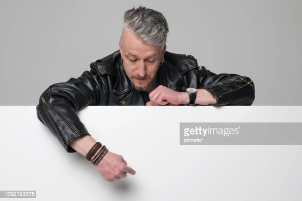 mature man pointing downward - long sleeved stock pictures, royalty-free photos & images