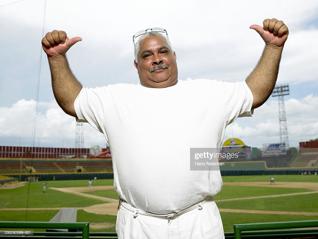mature man pointing to self in baseball stadium portrait stock photo